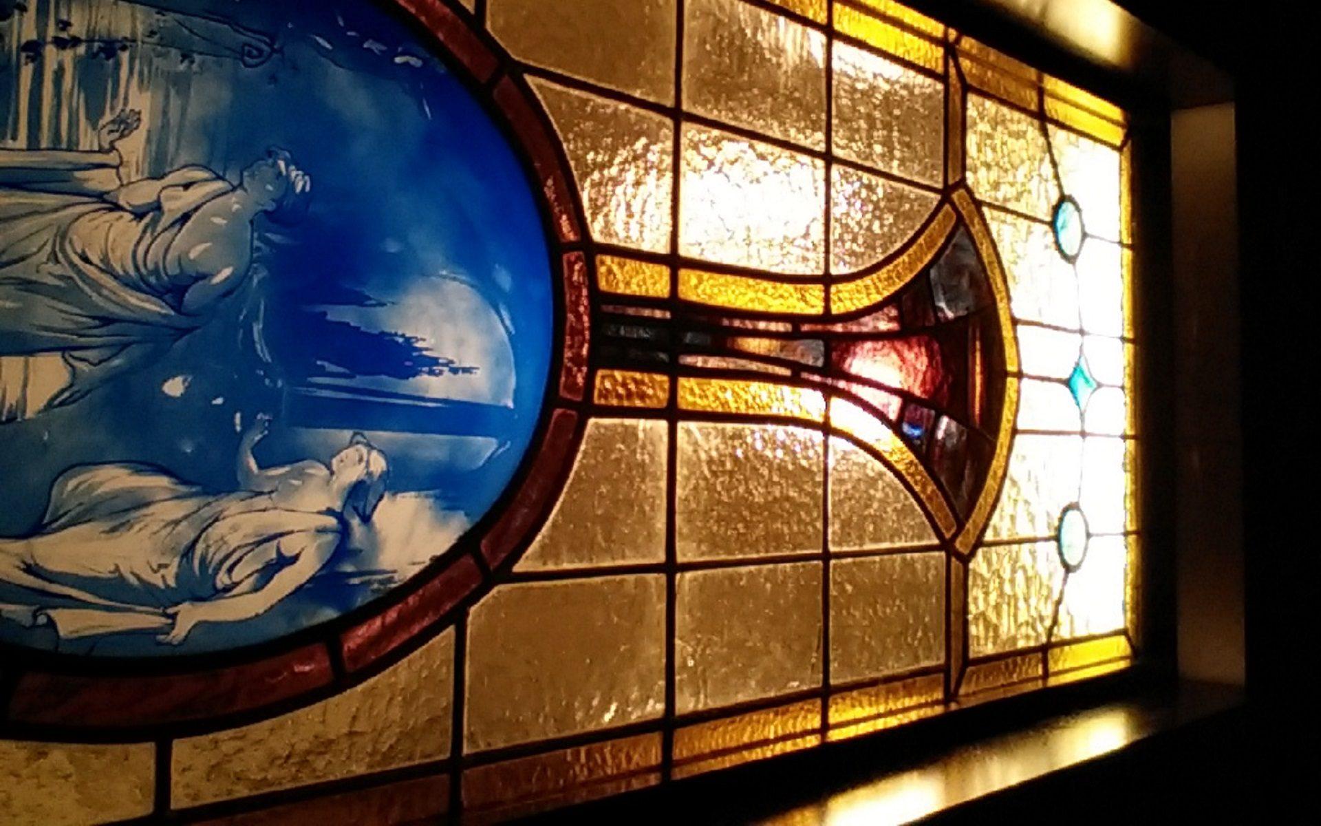 一般住宅の室内にはめ込まれたアンティークのステンドグラスウィンドウを仰ぎ見る。イラストはエッチング処理で表現されている。